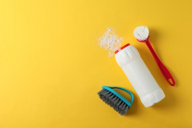 Bottle with detergent powder and brushes on yellow background, space for text