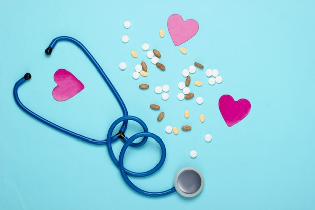 Bottle with different pills, heart and stethoscope on blue