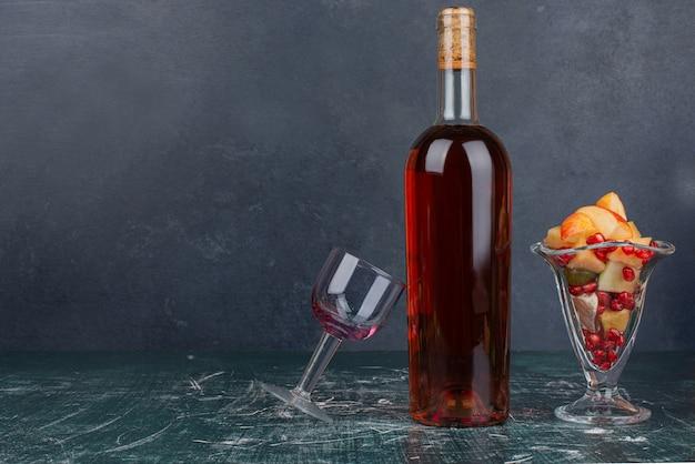 Бутылка с пустым стаканом и тарелкой яблока