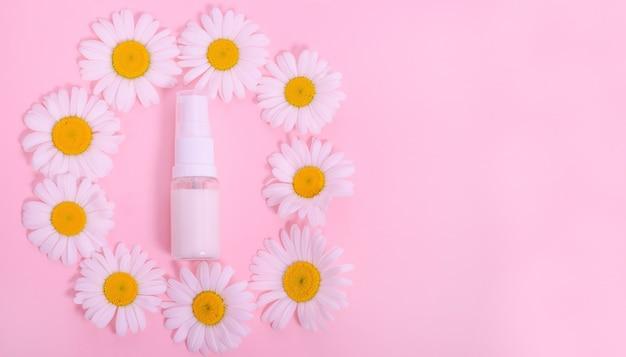 コピースペースとピンクの背景にカモミールの花と顔またはボディクリームのボトル