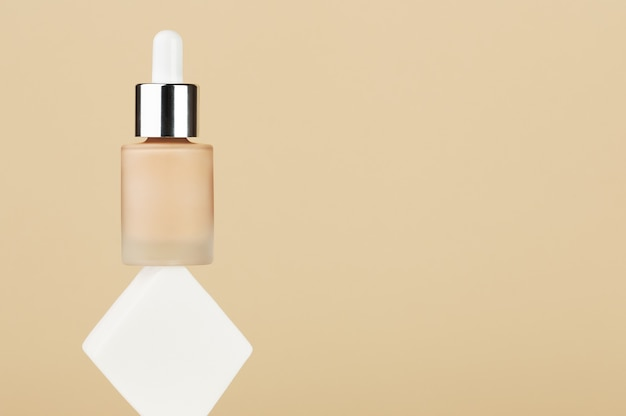 Bottle with foundation liquid beige cream balance on white square sponge. professional makeup product for perfect complexion. woman accessories, base beauty product, primer, concealer. copy space.