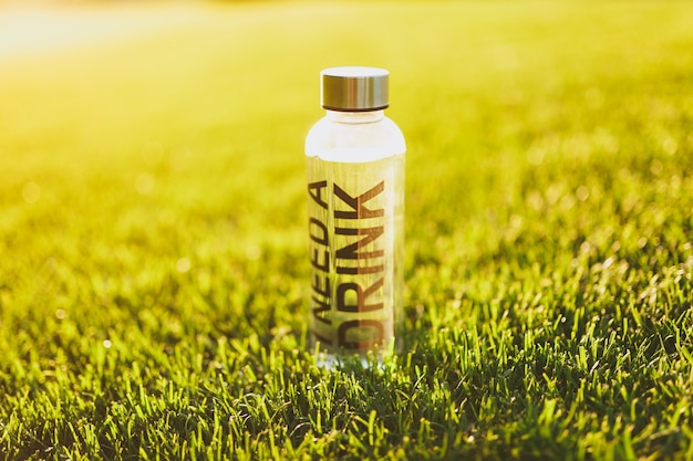 햇빛 잔디에 있는 푸른 잔디에 음료가 필요하다는 문구가 적힌 신선하고 깨끗한 투명한 물이 담긴 병. 자연 질감, 녹색 배경, 벽지입니다. 축구장 또는 스포츠 컨셉 디자인.