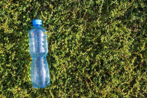 푸른 잔디에 신선하고 깨끗한 물이 담긴 병. 상위 뷰, 복사 공간