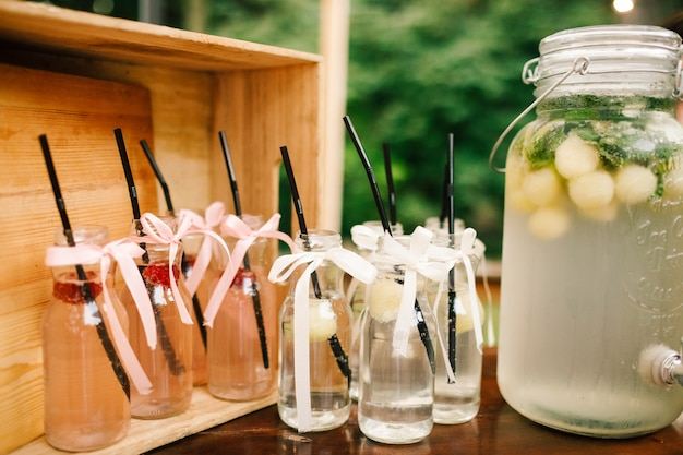 Bottle with fresh lemonade and glasses around it stands on the dinner table in the garden