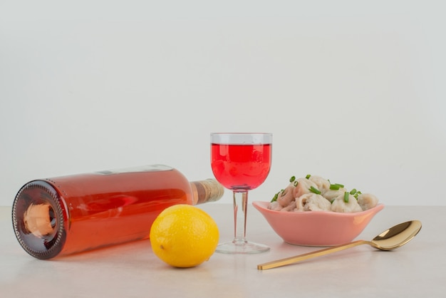 Bottle with glass of lemonade and plate of dumplings .