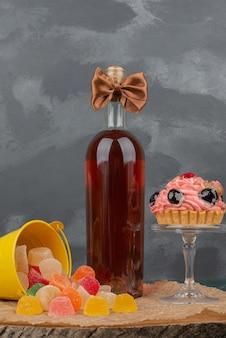 Bottiglia con lastra di vetro di ciambella e caramelle di gelatina su tavola di legno