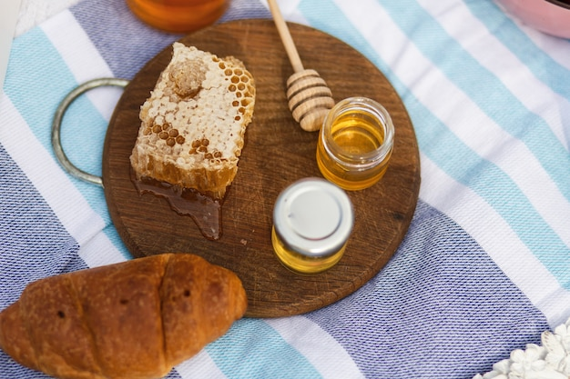 Bottle with honey, bagel and honeycomb on a wooden plate.