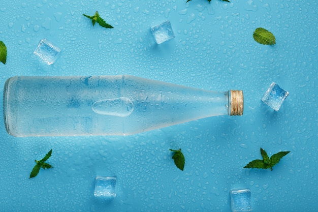 Bottle with an ice cold beverage, ice cubes, drops and mint leaves