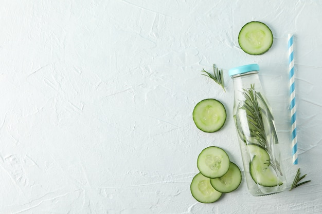 Bottle with infused cucumber water on white background, space for text