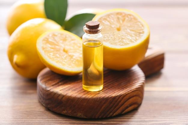 Бутылка с эфирным маслом лимона на деревянном столе