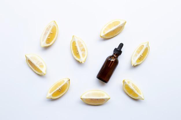 Bottle with lemon essential oil on white