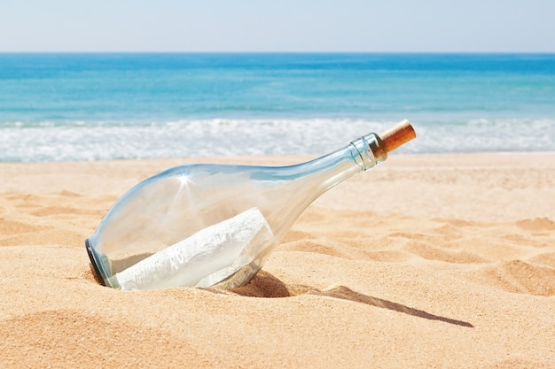 A bottle with a letter of distress on the beach. summer.