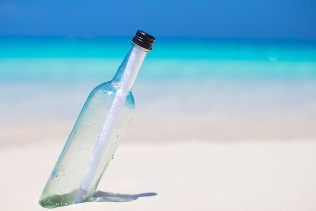 Bottle with a message buried in the white sand