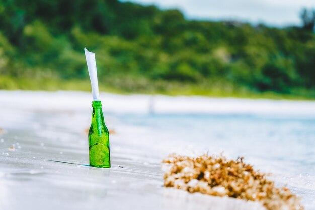 흐리게 정글과 하얀 낙원 모래 해변에 메시지와 함께 병
