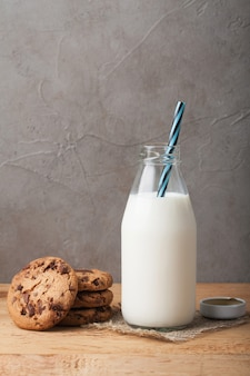 Bottle with milk and chocolate chip cookies.
