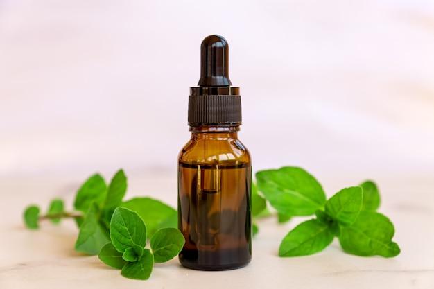 민트 에센셜 오일과 녹색 잎이 든 병