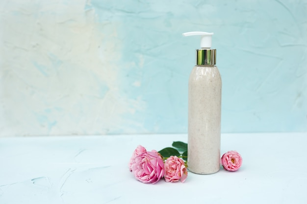 Bottle with natural scrub and pink flowers on pastel blue textured background. skincare cosmetic, beauty spa concept.