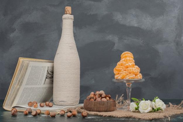 Бутылка с орехами и стеклянная тарелка мандарина.