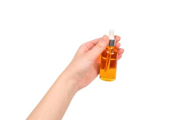 Бутылка с маслом в руке женщины, изолированные на белом. скопируйте пространство.