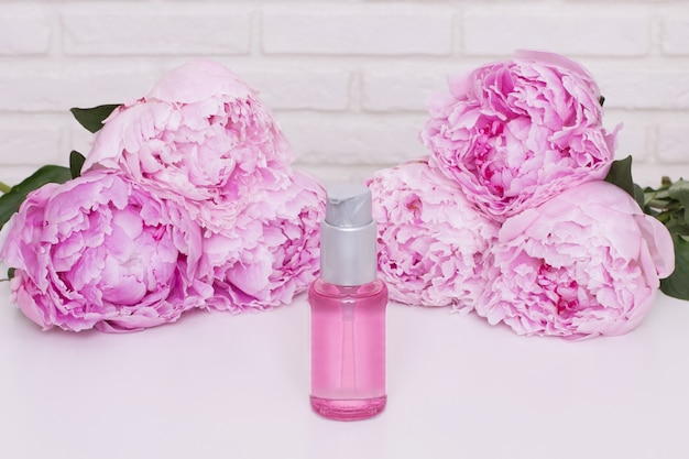 Bottle with oil for skin and hair care on pink peonies