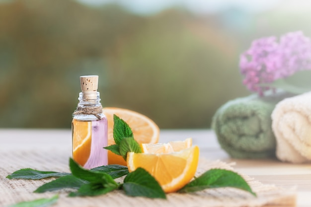 Bottle with orange oil, orange and fresh green mint leaves on wooden table. towels for spa and lilac in blurred natural background.  selective focus.