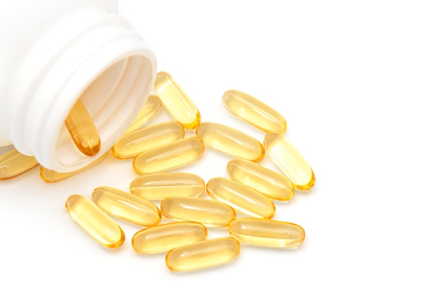 Bottle with pills of omega or fish oil on white background