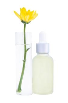 ピペットと白い背景で隔離の試験管に花が入ったボトル
