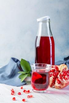 Бутылка с гранатовым соком и стакан, спелый гранат, целые и очищенные на белом фоне деревянные