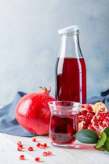Bottle with pomegranate juice and a glass, ripe pomegranate, whole and peeled on a white wooden