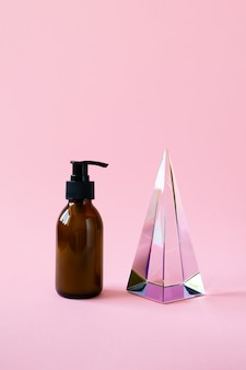 Bottle with pump for beauty product mockup and glass pyramid prism on pink background