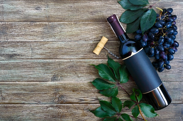 Bottle with red wine corkscrew blue grapes leaves on a wooden table