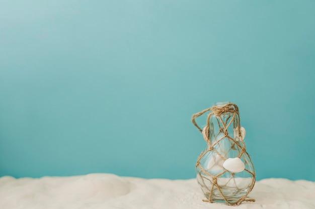 Бутылка с веревкой на песке
