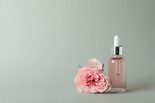 Бутылка с эфирным маслом розы и розой на светло-сером