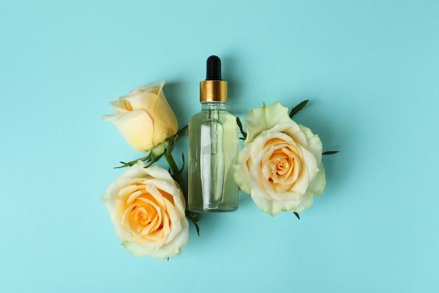 Бутылка с эфирным маслом розы и розами на синем
