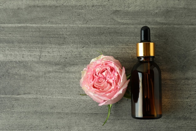 Бутылка с эфирным маслом розы на сером текстурированном столе