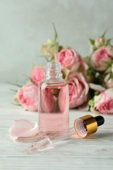 Бутылка с эфирным маслом розы на белом деревянном столе