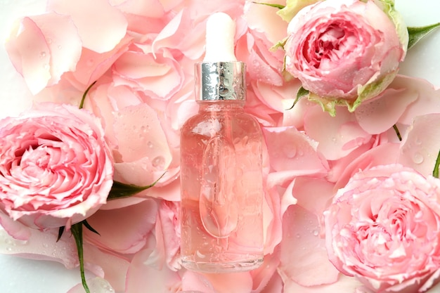 Bottle with rose essential oil on rose petals