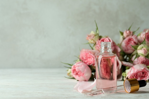 Bottle with rose essential oil on white wooden table
