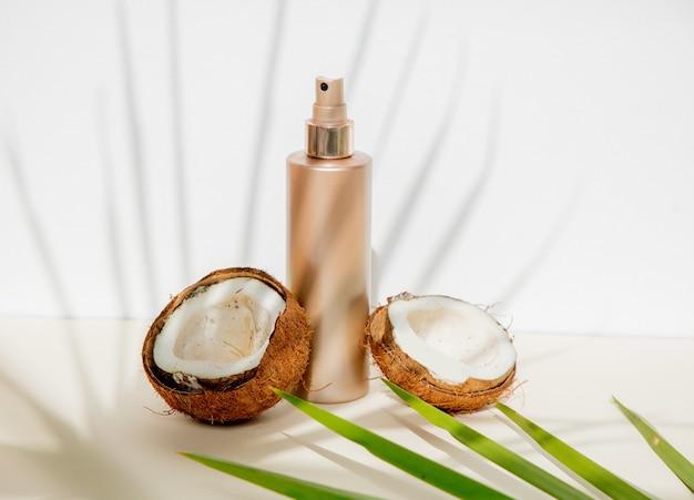 白い背景の上のスキンケアクリームとココナッツのボトル