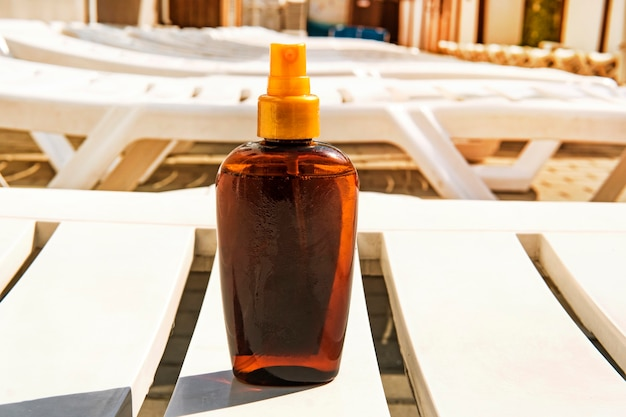 Bottle with suntan cream on deckchair. sunburn and cancer prevention concept. copy space. place for text on bottle. suntan oil.