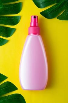 モンステラの葉で飾られた、黄色の背景に分離された日焼け止めクリームの瓶。
