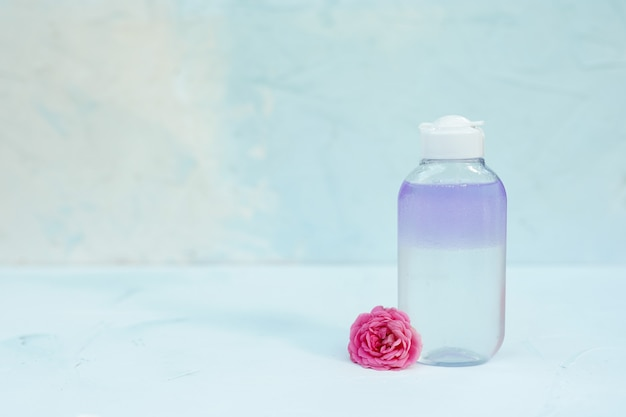 Bottle with tonic or micellar water for skincare on light blue textured background with little pink flower