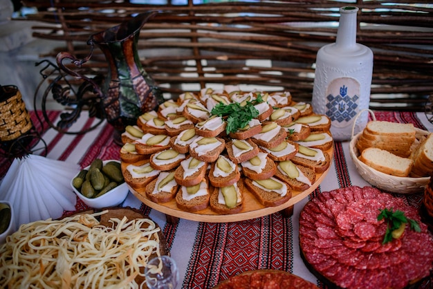 Bottle with vodka and plates with pickled vegetables and meat stand on the table