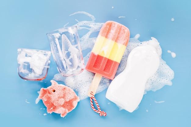 비누 거품 배경에 아이스크림과 유리의 형태로 세척제와 스폰지가 있는 병. 설거지 개념입니다. 평면 위치, 상위 뷰.