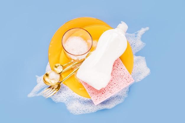 비누 거품 배경에 세척제, 스폰지, 노란색 접시가 있는 병. 설거지 개념입니다. 평면 위치, 상위 뷰.
