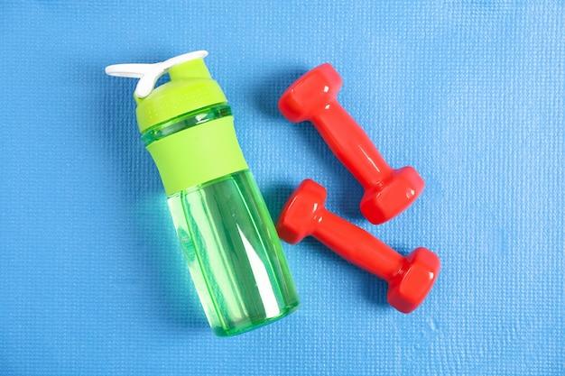 青とトップビューで水と赤のダンベルのボトル