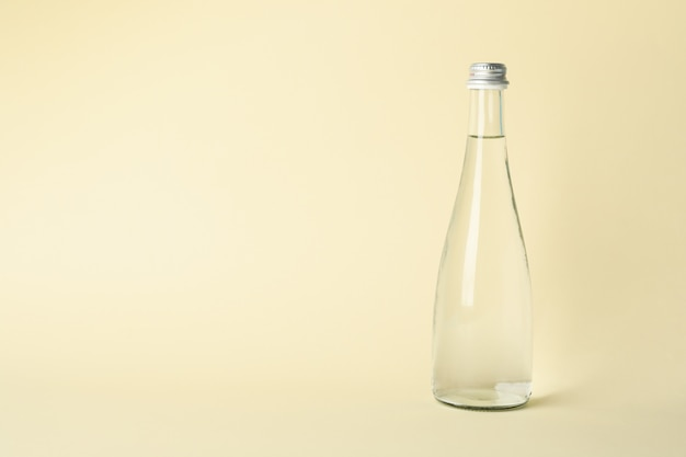 Bottle with water on beige, space for text