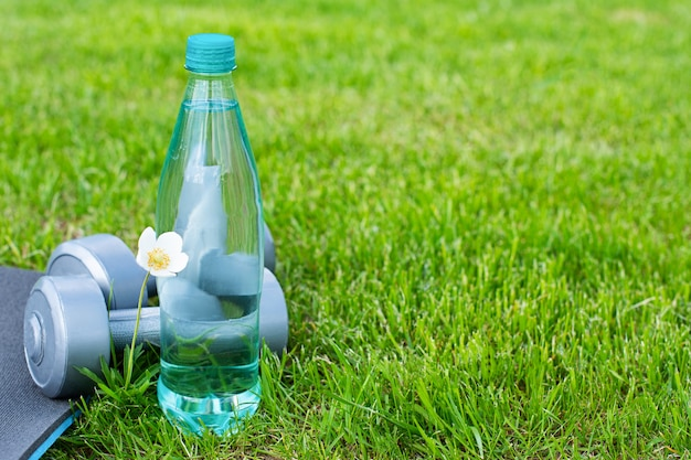 물, 아령, 스포츠 및 녹색 잔디에 요가 매트 병. 공간 복사