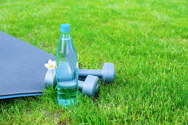 Bottle with water, dumbbells and a mat for sports and yoga on the green grass. copy space