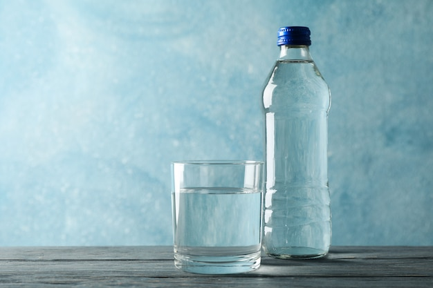 Bottle with water and glass on wooden table, space for text